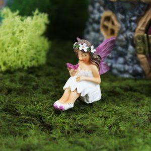 Petite figurine de fée tenant un papillon pour jardin de fées et terrarium.